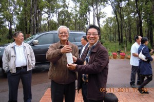 Mr Edward Kuh receiving the bottle of premium wine brought by Honorary Advisor Mr Francis Yapp and his Mrs Agnes, while Mr Chris HP Wong 黄汉平 looks on
