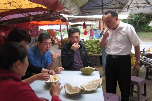 Eating the roadside durians by the road. All attention seems to be on tasting the durian