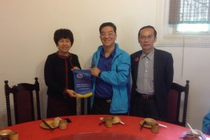 Presenting a pennant to Ms Cai, Chairman of the Returned Overseas Chinese Association in Meizhou 赠送锦旗给梅州侨联主席蔡女士